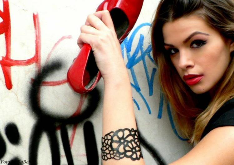 Testimonial con braccialetto e scarpa rossa contro la violenza